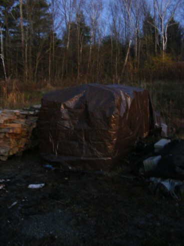 Covering the wood pile with a tarp.